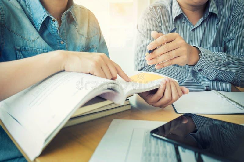 De jonge studentencampus helpt vriend het de achterstand inlopen en het leren tuto stock afbeeldingen