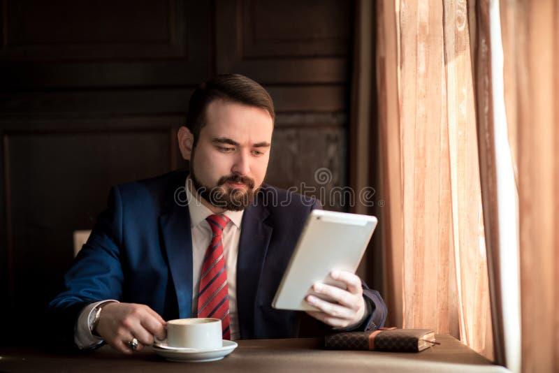 De jonge succesvolle zakenman leest het nieuws op tablet royalty-vrije stock foto's