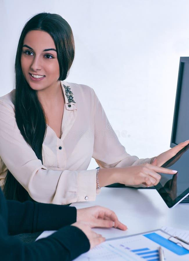 De jonge tablet van de bedrijfsvrouwenholding en het bespreken van bepaald geval met haar collega stock foto