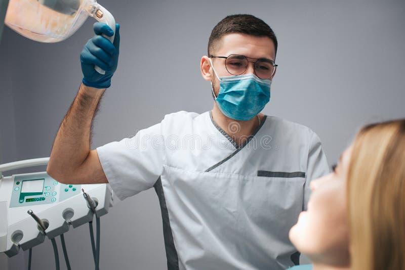 De jonge tandarts in masker zit bij cliënt en greeplamp De jonge vrouw bekijkt arts en glimlach Zij zijn in tandheelkunderuimte royalty-vrije stock foto's