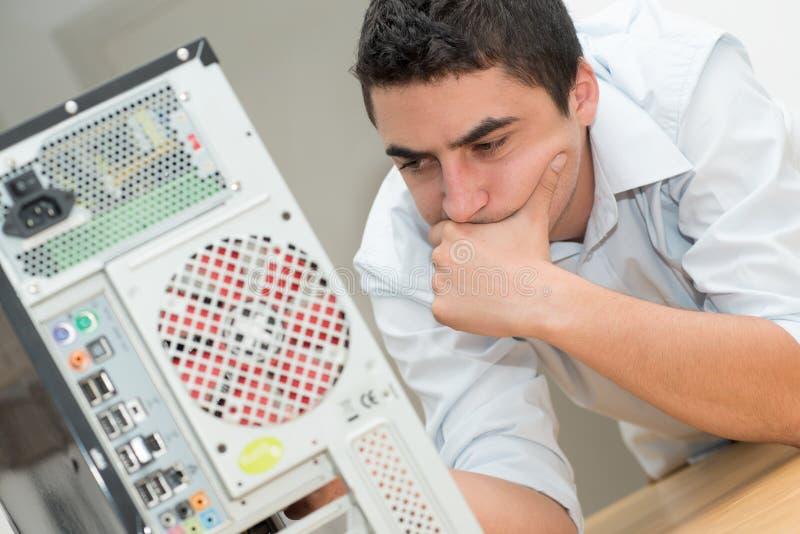 De jonge technicus heeft een probleem met computer stock foto