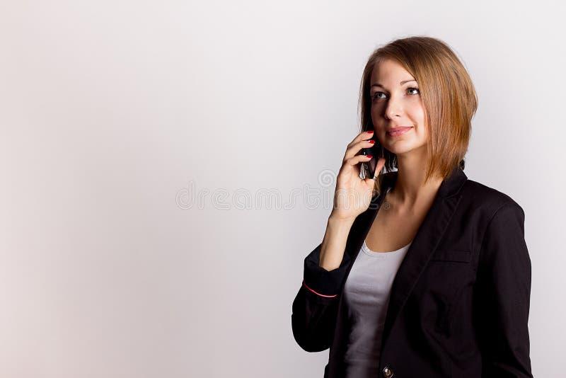 De jonge telefoon van de onderneemsterholding stock foto