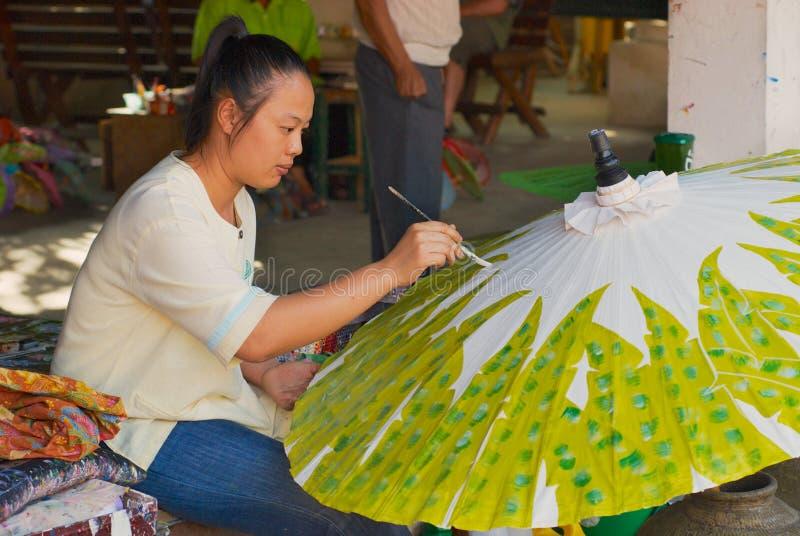 De jonge Thaise vrouw schildert traditionele bamboeparaplu bij de fabriek in Chiang Mai, Thailand stock foto's