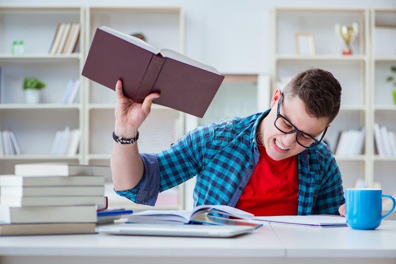 De jonge tiener die voor examens voorbereidingen treffen die bij een bureau binnen bestuderen stock afbeeldingen