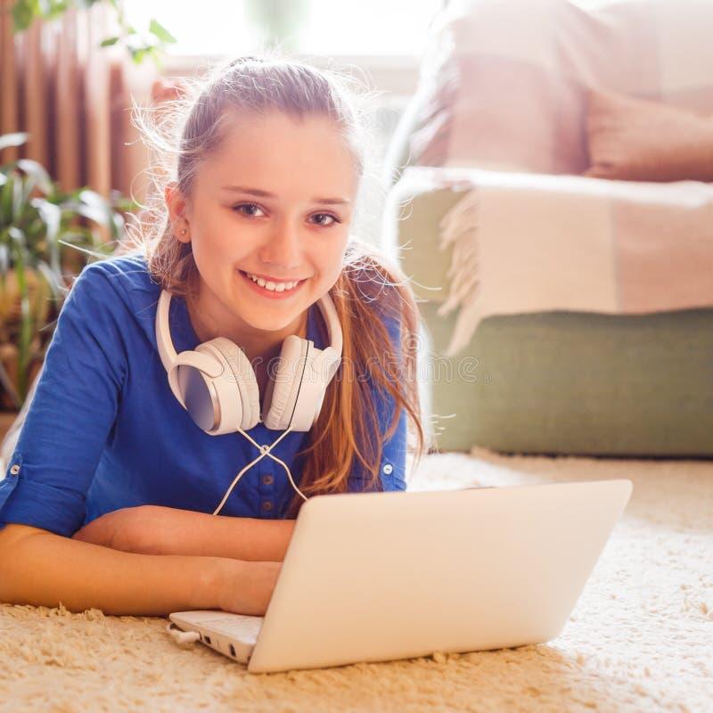De jonge tiener heeft pret die laptop thuis met behulp van royalty-vrije stock afbeeldingen