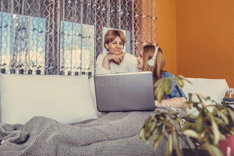 De jonge tiener heeft pret met haar moeder die laptop thuis met behulp van royalty-vrije stock foto