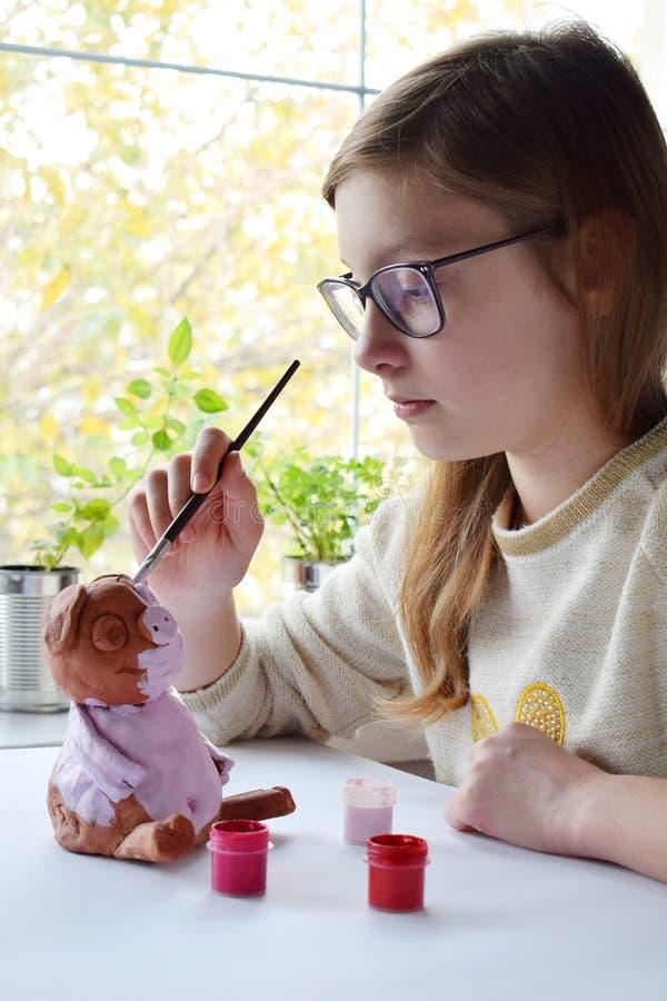 De jonge tiener maakt stuk speelgoed, schildert kleivarken met gouache Creatieve Vrije tijd voor kinderen Ondersteunende creativi stock foto's
