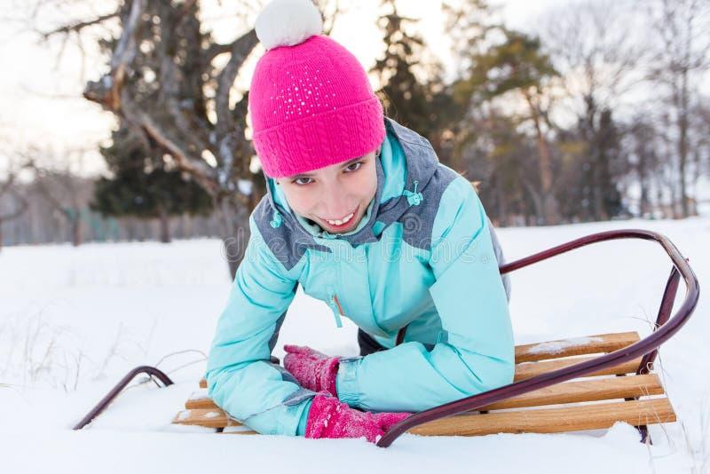 De jonge tiener met slee heeft pret in sneeuw royalty-vrije stock afbeeldingen