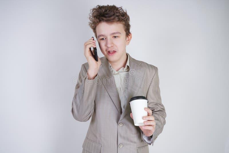 De jonge tiener met verraste emoties in grijze zaken kleedt status met mobiele telefoon en document kop van koffie op witte studi royalty-vrije stock foto's