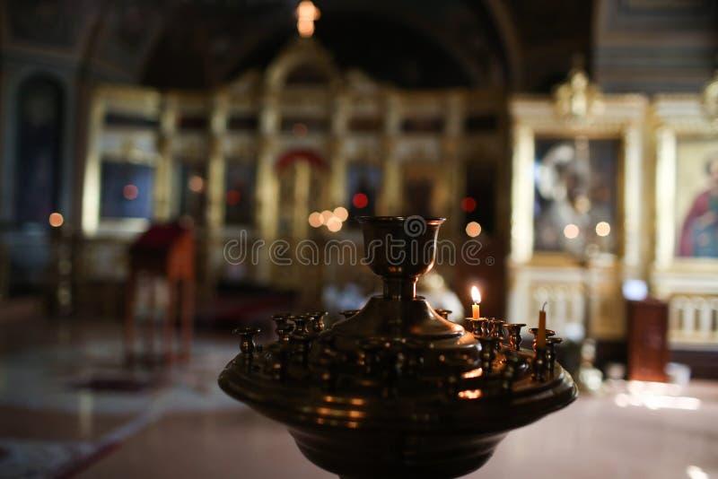 De jonge tienerlichten een kerkkaars voor meditatie en bidden stock afbeelding