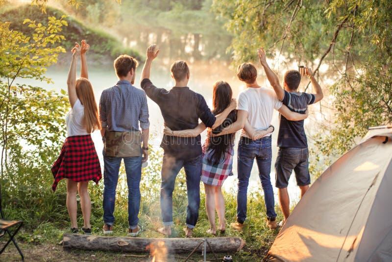 De jonge toeristen verenigen zich wapen in wapen en hebben pret dichtbij het meer royalty-vrije stock afbeelding