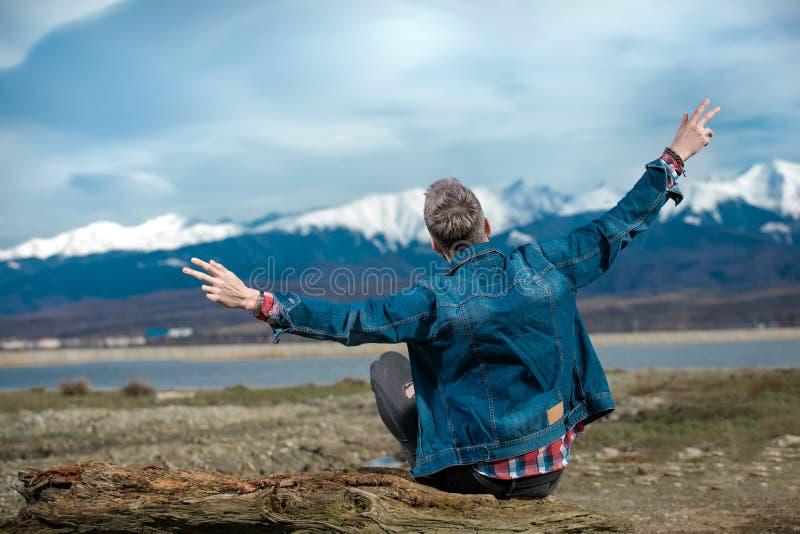 De jonge toevallige mens zit op houten logboek en viert vrijheid stock fotografie