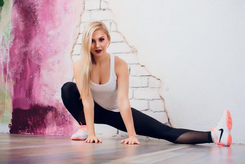 De jonge trainer van de de vrouwengeschiktheid van het blondemeisje toont de oefening stelt stock afbeelding