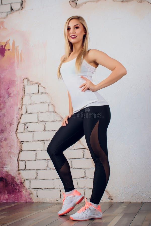De jonge trainer van de de vrouwengeschiktheid van het blondemeisje toont de oefening stelt royalty-vrije stock foto's