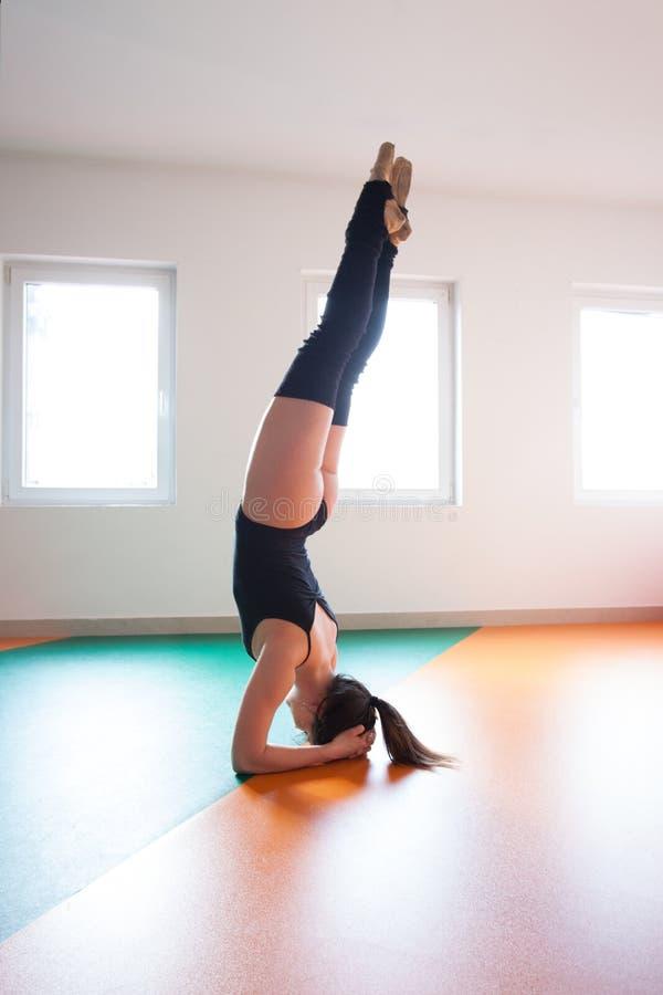 De jonge tribune van de balletdanserpraktijk op hoofd stock fotografie
