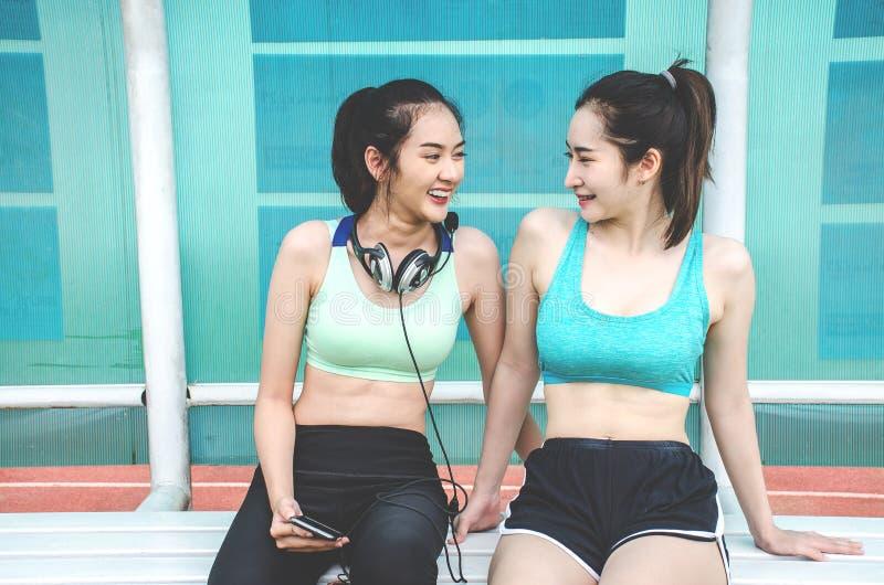 De jonge twee vrienden die van sportenvrouwen bij het park zitten en na openlucht aanstoten ontspannen En zij die spreken lachen stock afbeelding