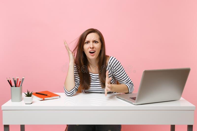 De jonge uitgeputte geïrriteerde vrouw in verbijstering het uitspreiden handen zit, werkt bij wit bureau met eigentijdse PC-lapto royalty-vrije stock fotografie
