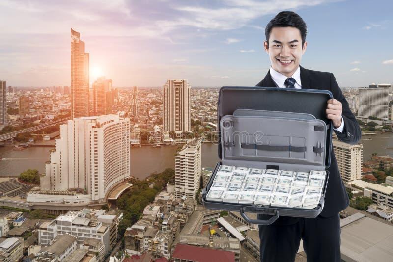 De Jonge uitvoerende man die een bagage met bankbiljet op citys houden royalty-vrije stock afbeeldingen