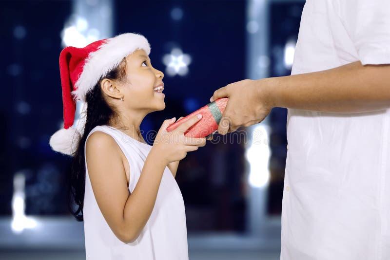 De jonge vader geeft een Kerstmisgift aan zijn dochter royalty-vrije stock afbeelding