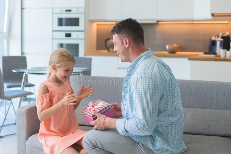 De jonge vader geeft zijn dochter een gift stock fotografie
