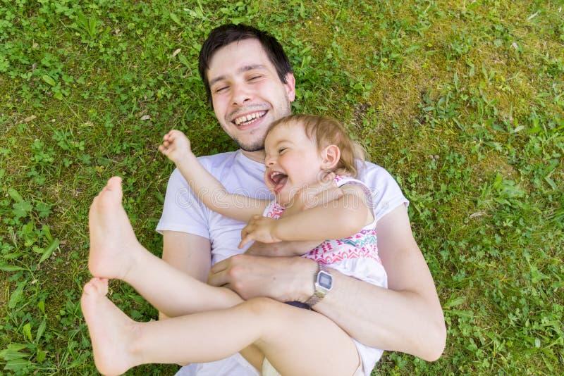 De jonge vader heeft pret met zijn kleine dochter De mens en het kind spelen in gras royalty-vrije stock afbeeldingen