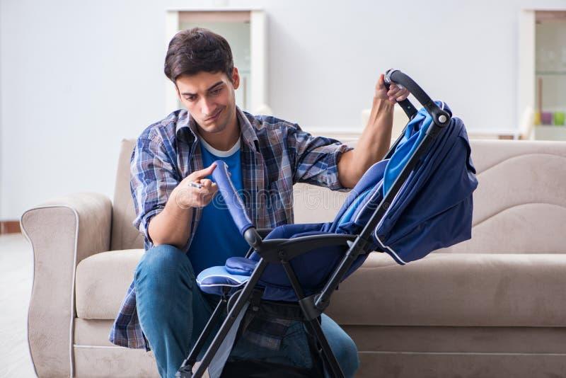De jonge vader het assembleren babykinderwagen thuis stock foto
