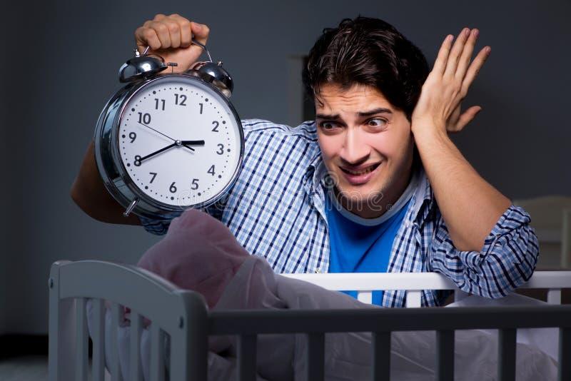 De jonge vader onder spanning toe te schrijven aan baby het schreeuwen bij nacht stock afbeeldingen