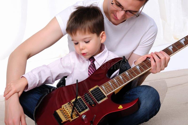 De jonge vader onderwijst zijn jonge zoon royalty-vrije stock afbeeldingen