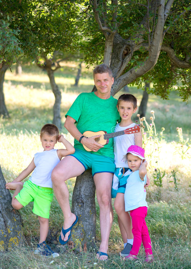De jonge vader speelt de gitaar voor zijn jonge kinderen in het bos stock afbeelding