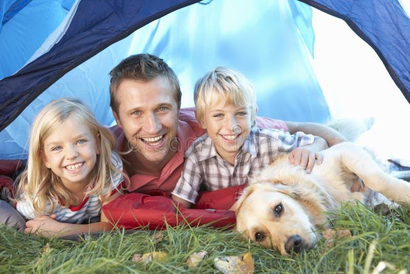 De jonge vader stelt met kinderen in tent royalty-vrije stock afbeelding