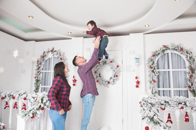 De jonge vader werpt omhoog weinig zoon met moeder in Kerstmisdecor royalty-vrije stock afbeelding