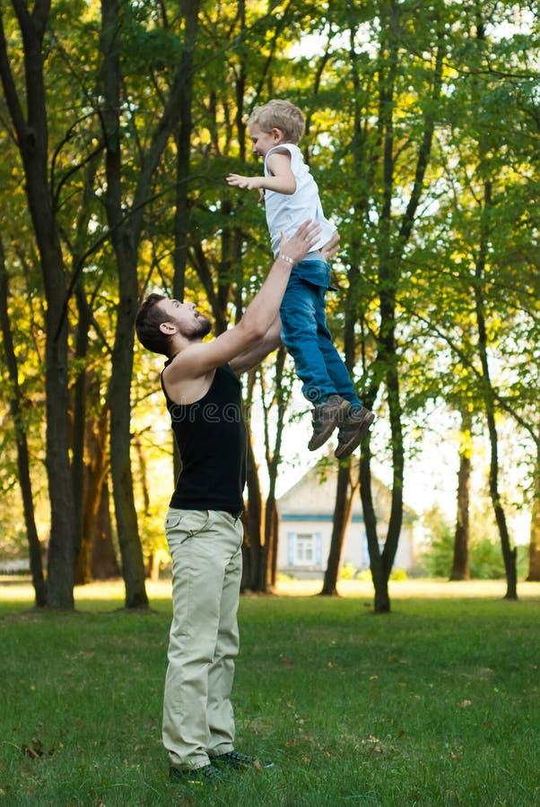 De jonge vader wierp zijn zoonshoogte in de hemel stock fotografie