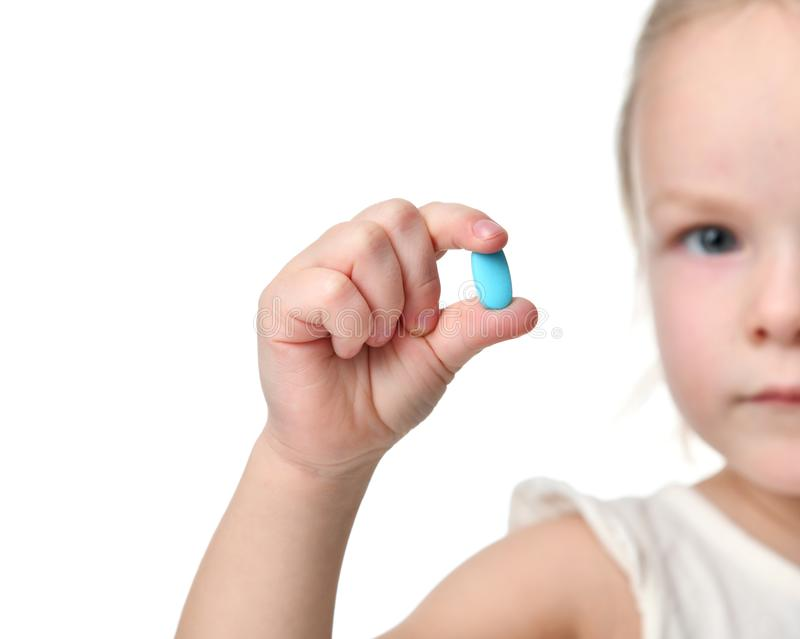 De jonge van de de greep lichtblauwe hoofdpijn van het babymeisje tablet van de de pillengeneeskunde in kleine hand royalty-vrije stock foto's