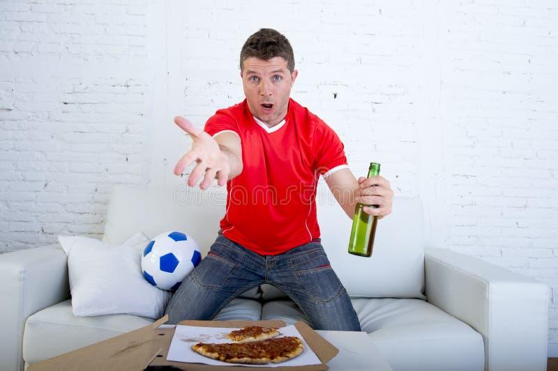 De jonge verdedigersmens met bal en bierfles het letten op voetbalspel op televisiezitting gaat liggen thuis royalty-vrije stock fotografie