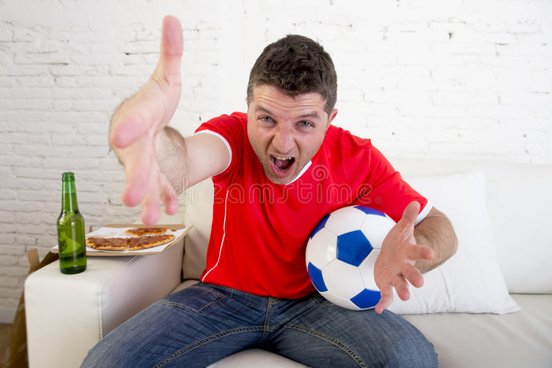 De jonge verdedigersmens met bal en bierfles het letten op voetbalspel op televisiezitting gaat liggen thuis stock afbeelding