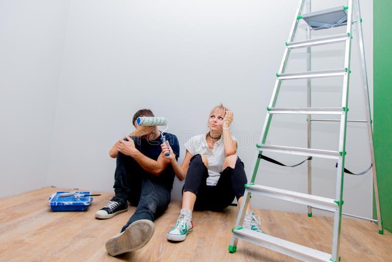 De jonge vermoeide familie probeert om een muur in hun ruimte te schilderen royalty-vrije stock foto