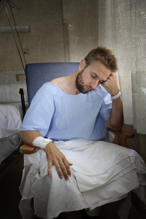 De jonge verwonde mens in de zitting van de het ziekenhuisruimte alleen in pijn maakte zich voor zijn gezondheidsvoorschrift onge stock foto's
