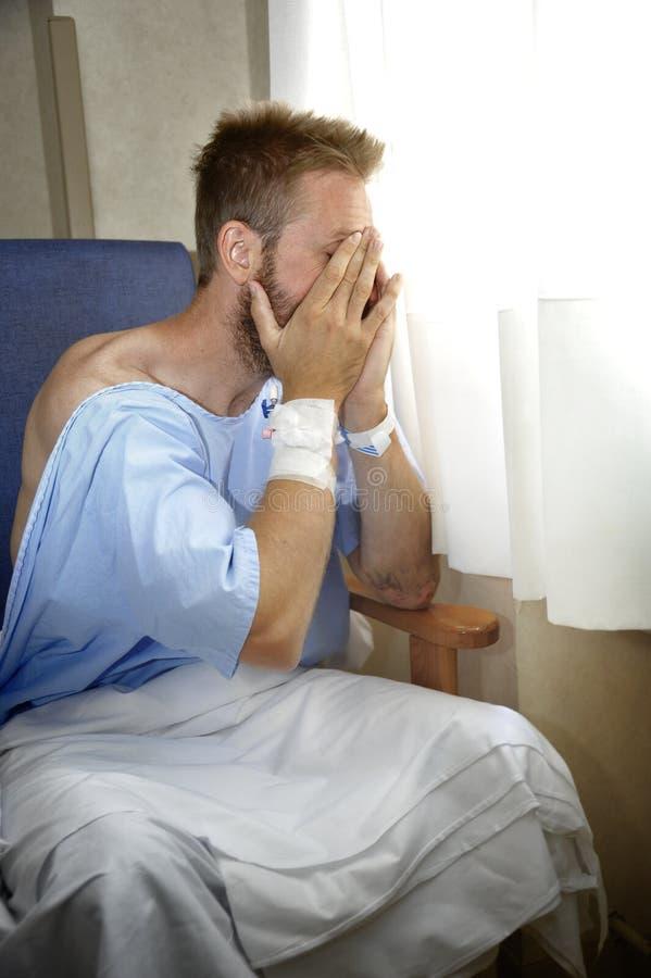 De jonge verwonde mens die in het ziekenhuisruimte schreeuwen die alleen het schreeuwen in pijn zitten maakte zich voor zijn gezo stock foto