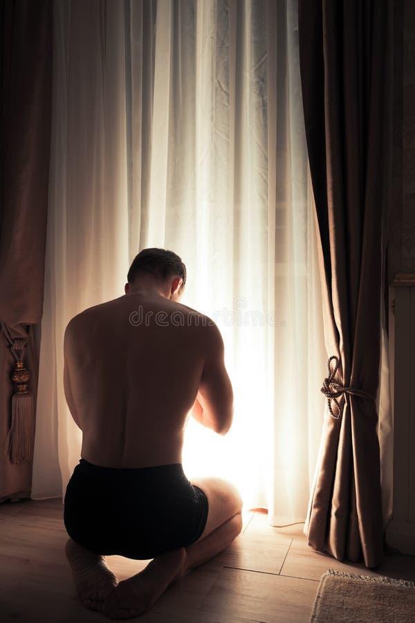De jonge volwassen biddende mens zit dichtbij venster royalty-vrije stock afbeelding