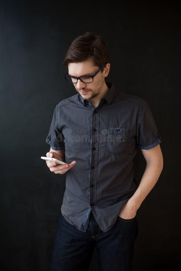 De jonge volwassen kerel in een grijs overhemd gebruikt een smartphone Bedrijfsportret op geweven zwarte achtergrond stock afbeeldingen