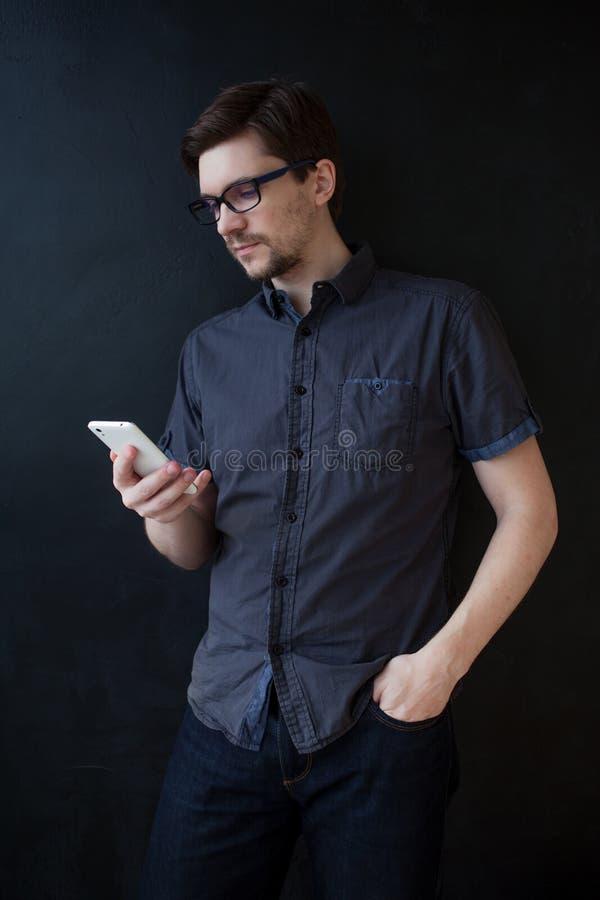 De jonge volwassen kerel in een grijs overhemd gebruikt een smartphone Bedrijfsportret op geweven zwarte achtergrond royalty-vrije stock foto's