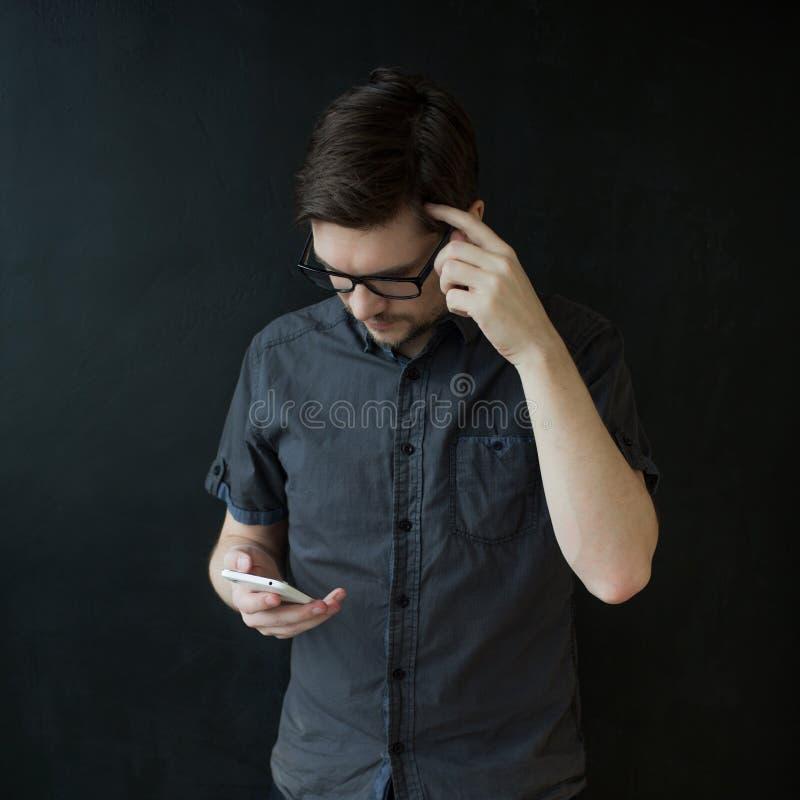 De jonge volwassen kerel in een grijs overhemd gebruikt een smartphone Bedrijfsportret op geweven zwarte achtergrond royalty-vrije stock afbeelding