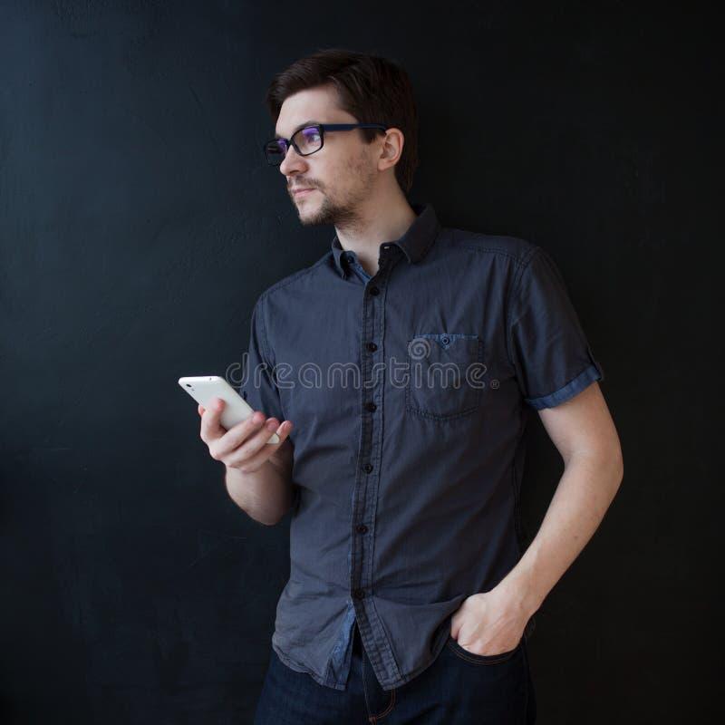 De jonge volwassen kerel in een grijs overhemd gebruikt een smartphone Bedrijfsportret op geweven zwarte achtergrond stock foto