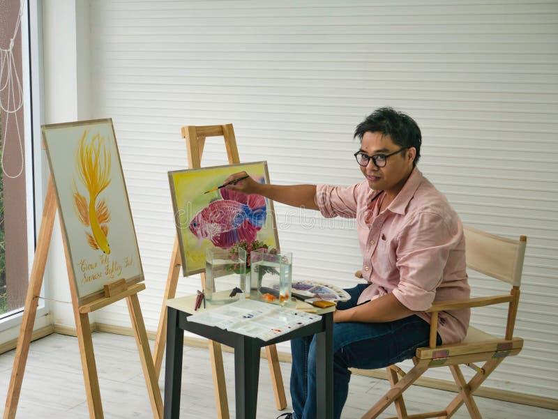 De jonge volwassen Mannelijke waterverfkunstenaar Feeding de vissen terwijl het trekken van de vissen schildert, stock foto's
