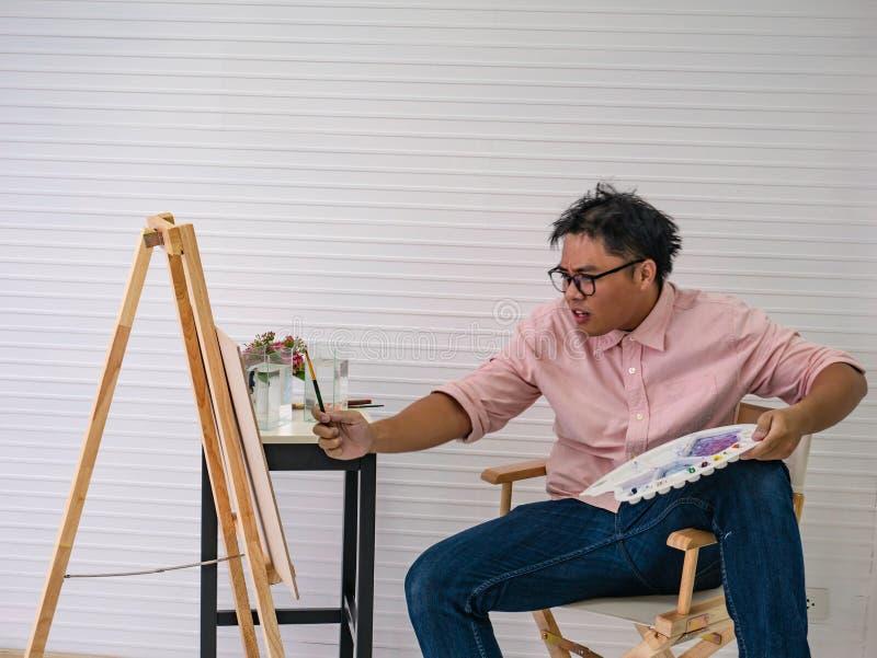 De jonge volwassen Mannelijke waterverfkunstenaar Feeding de vissen terwijl het trekken van de vissen schildert, royalty-vrije stock foto's