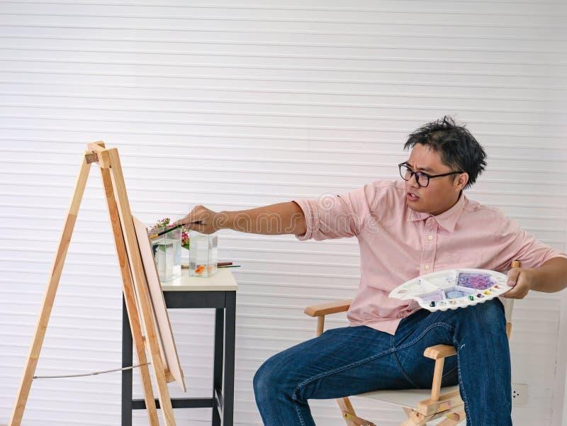 De jonge volwassen Mannelijke waterverfkunstenaar Feeding de vissen terwijl het trekken van de vissen schildert, stock fotografie