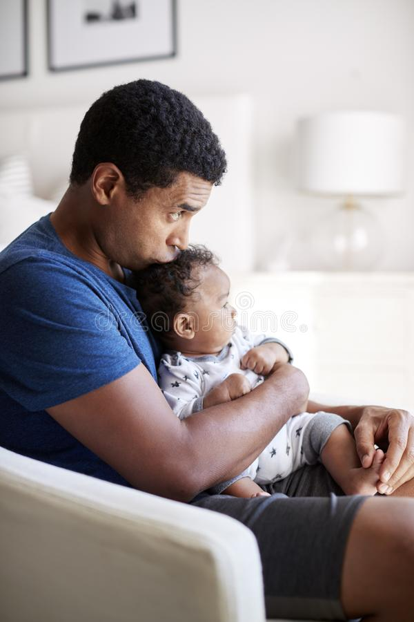 De jonge volwassen vaderzitting in een leunstoel die zijn oude babyzoon houden van drie maanden en zijn hoofd, zijaanzicht kussen stock afbeelding