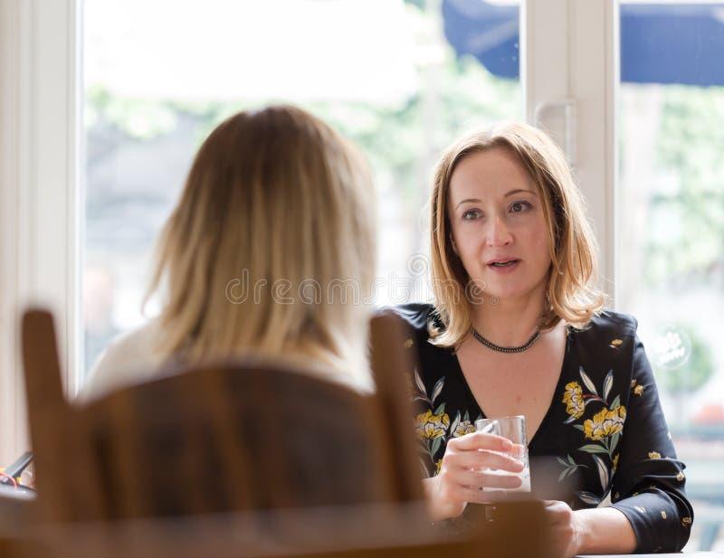 De jonge volwassen vrouw luistert aan tegenstander bij informele bedrijfsmeetin stock afbeelding
