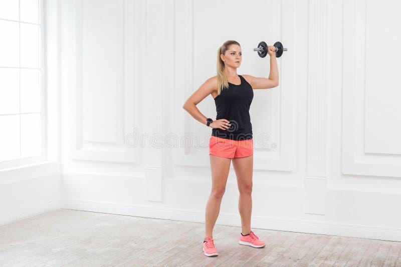 De jonge volwassen vrouw van de motivatie atletische mooie bodybuilder in roze borrels en zwarte hoogste status, die dumbells doe royalty-vrije stock afbeelding
