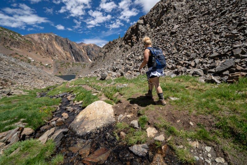 De jonge volwassen vrouwenwandelaar loopt langs de vuilweg door de bergen in Siërra Nevada California stock foto's
